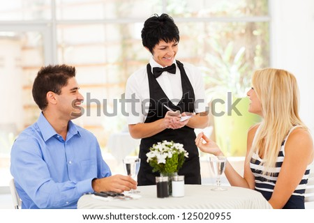 friendly middle aged waitress taking order from customer in restaurant