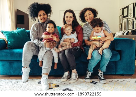 Friendly moms with babies sitting on sofa at home. Club of young mothers.