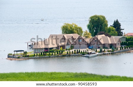 Friendly neighborhood of houses at the lake. - stock photo