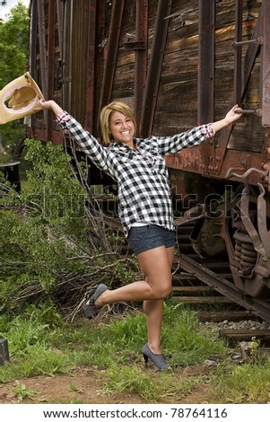 friendly, nice, country girl waving a cowboy hat in the air.