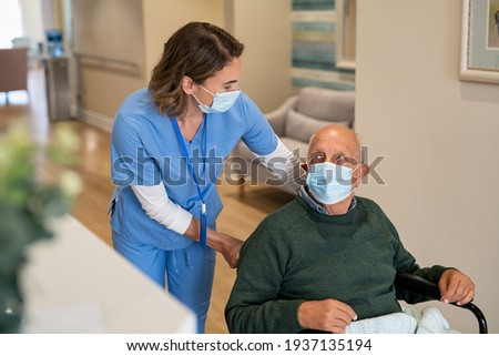 Friendly nurse wearing protective face mask helping handicapped senior man in wheelchair at hospital during covid19 pandemic. Nurse with surgical mask taking care of an elderly patient on a wheelchair
