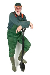 Friendly older gardener in his green work clothes, leaning on his spade in front of a white background and laughs heartily at the camera.