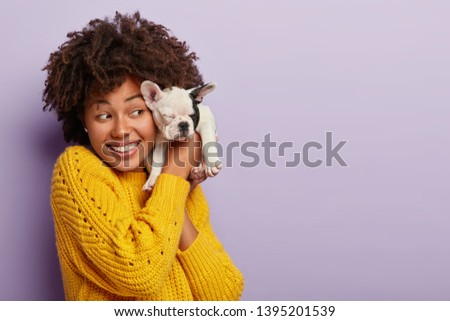 Friendly optimistic woman chills with small puppy, holds french bulldog near face, have happy good day, pose indoor against purple background. Woman dog lover plays with sweety pedigree pet. #1395201539
