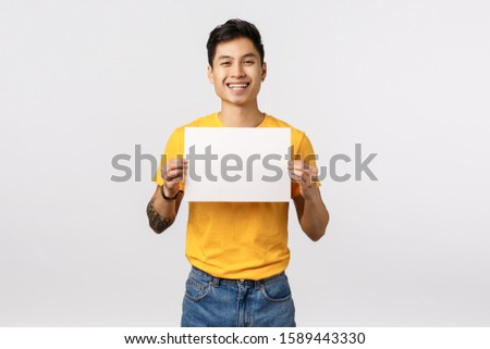 Friendly, outgoing and cheerful young asian man in yellow t-shirt, holding blank empty piece paper, smiling from overjoy, write confession or statement, showing corporate promo, white background