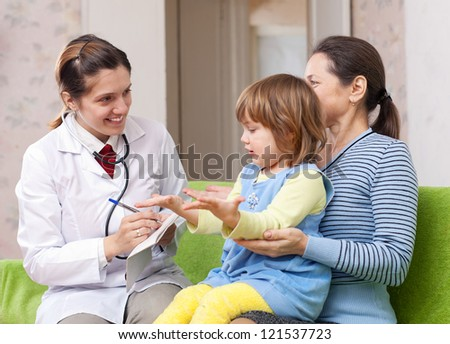 friendly pediatrician doctor examining baby girl. Focus on adults