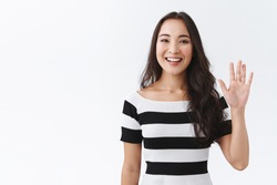 Friendly, pleasant and cheerful east-asian woman in striped t-shirt raising palm, wave hand greeting, saying hi or hello and smiling with joyful expression as welcoming newbies, white background
