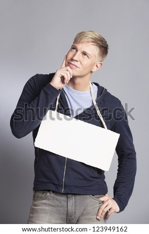 Friendly pondering man presenting white empty signboard with space for text isolated on grey background.