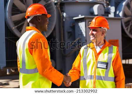 friendly power company co-workers hand shaking in electrical substation