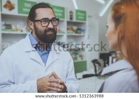 Friendly professional pharmacist talking to his female customer at the drugstore. Unrecognizable woman buying medicine at pharmacy. Service, healthcare, consumerism concept