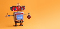 Friendly robot toy with key padlock on orange background. Cyborg smiley face, red head blue monitor body. digital message closed. copy space