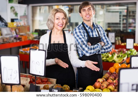 friendly sellers posing with fruits in local supermarket
