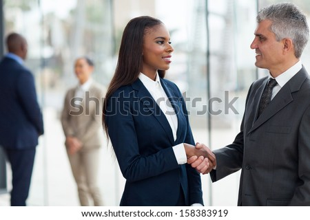 friendly senior businessman handshaking with young businesswoman in office