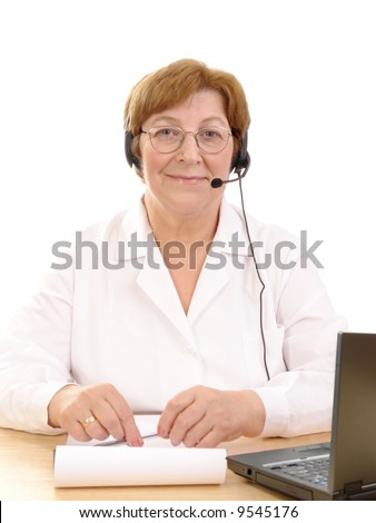 Friendly senior family doctor wearing headset sitting behind a desk with laptop over white background