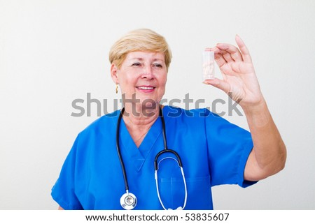 friendly senior female doctor holding out a bottle of pills on white background