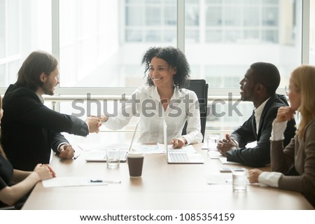 Friendly smiling african businesswoman handshaking caucasian businessman at diverse group meeting, mixed race black female boss welcoming new partner or executive team member shaking hands   boardroom