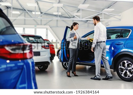 Friendly, smiling female seller showing brand new car to a customer while standing in car salon.