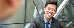 Friendly smiling handsome Asian businessman sitting at office lounge talking with his colleague, panoramic banner