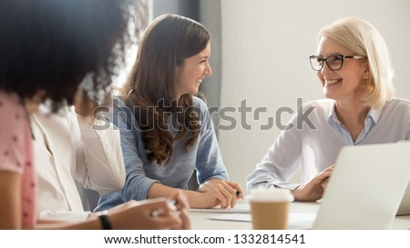 Friendly smiling old and young businesswomen talking laughing at corporate group business meeting, happy female employees colleagues coach manager and intern having fun pleasant conversation at work