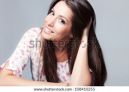 friendly smiling young woman portrait, hand in hair,   studio shot