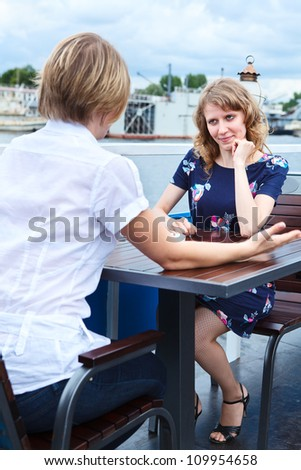 Friendly speaking two girlfriends at cafe table