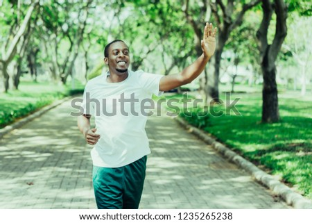 Friendly sporty black guy jogging in city park and greeting familiar sportsmen. Young Afro American man running outdoors and waving hand. Sport and communication concept