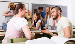Friendly  students 25 years old chatting while sitting in the room