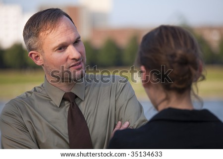 friendly talk between a businessman and woman on the street