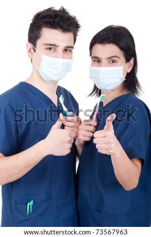 friendly team of dentists, doctors holding toothbrush and showing thumb up sign isolated on white background