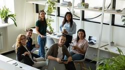 Friendly teammates. Group portrait of happy positive diverse business people employees executives managers having an informal meeting in modern office to discuss work affairs smiling looking at camera