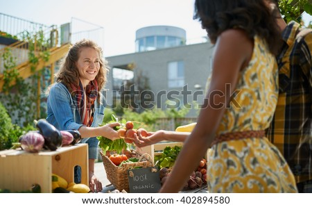 Friendly woman tending an organic vegetable stall at a farmer\'s market and selling fresh vegetables from the rooftop garden