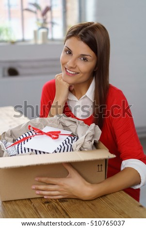 Friendly woman unpacking or packing a decorative gift tied with a ribbon and bow packaged in a cardboard box for mailing sitting at her kitchen table smiling at the camera #510765037