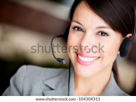Friendly woman working at a call center smiling