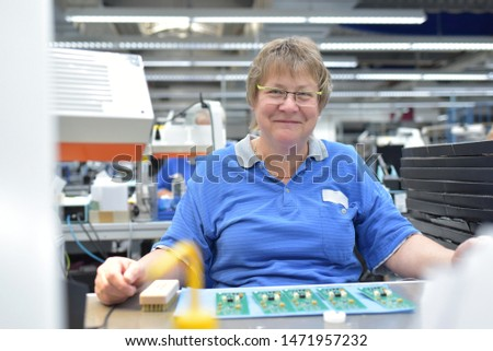 friendly woman working in a microelectronics manufacturing factory - component assembly and soldering