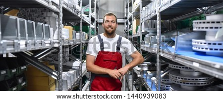 friendly worker in a warehouse and trade for car spare parts of a car repair shop  Foto stock ©
