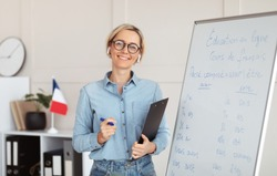 Friendly young female tutor standing near blackboard with French grammar rules, giving web lesson from home. Foreign language professor teaching students online. Remote education concept
