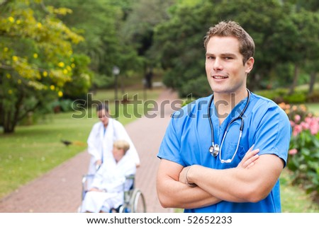 friendly young male doctor portrait outdoors, background is his colleague pushing recovery patient in wheelchair