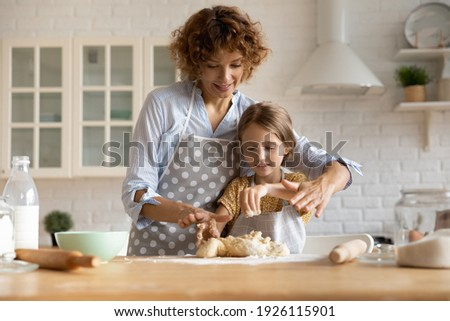 Friendly young mother little daughter cook dessert bakery at modern kitchen knead dough with hands enjoy preparing cookies bread spend time together. Small girl learn to bake with help of caring mom Photo stock ©