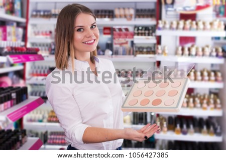 Friendly young saleswoman helping to choose powder in beauty store