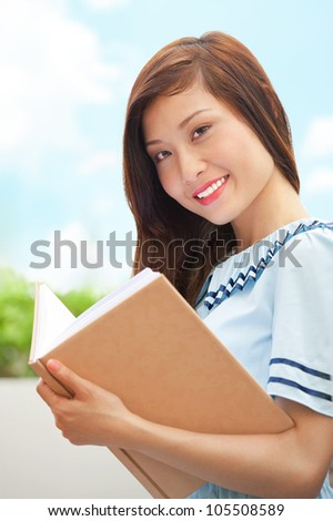 Friendly young student girl holding a book and looking at camera - stock photo