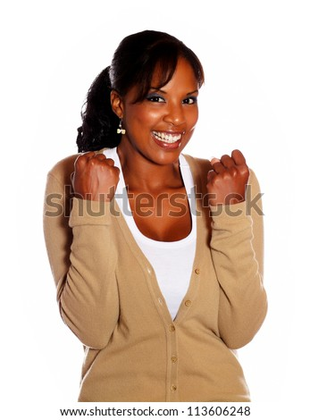 Friendly young woman celebrating a victory against white background