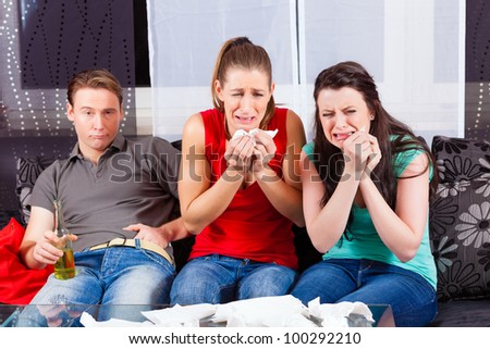 Friends - a man an two women - watching a sad movie in TV