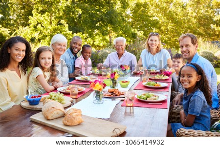 Friends and family having lunch in garden, looking to camera