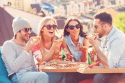 Friends and pizza. Four young cheerful people eating pizza and drinking beer while sitting at the bean bags on the roof of the building