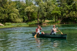 friends are canoeing in a wild river