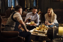 FRiends are enjoying drinks and food in a bar/restaurant. They are laughing and talking while eating burgers and drinking beer.