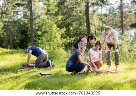 Friends Arranging Building Blocks On Grassy Field #701343595