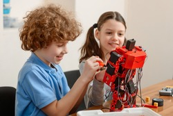 Friends assembles an electronic robot together. Boy and girl enjoy engineering classes, having fun and happy mood.