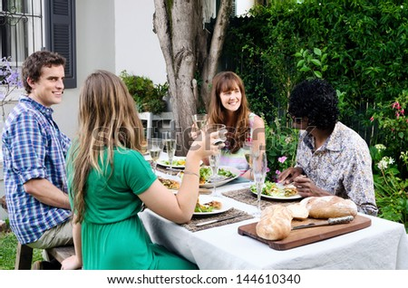 Friends at a party talking over food and wine