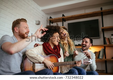 Friends at home enjoying singing and playing guitar. #732348022