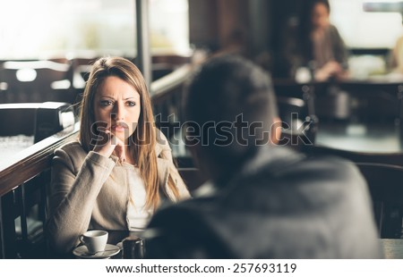 Friends at the bar, he is giving her bad news